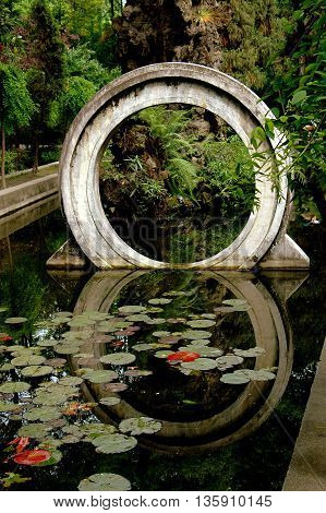 Chengdu China - May 8 2008: A traditional Chinese moon gate reflected in a pond filled with water lilies at the Wen Shu Temple gardens