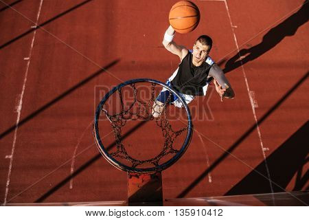 Handsome man peforming slum dunk action on a court.