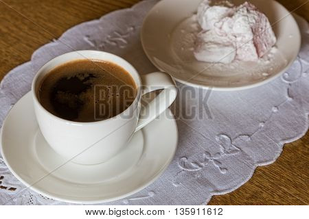 White cup of turkish coffee and small plate of lokum on wooden table