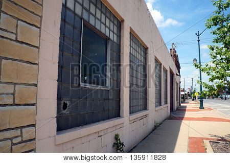 An abandoned building with a broken glass block in a glass block window in downtown Joliet, Illinois.