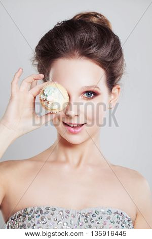 woman looking one eye and holing cake