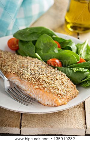 Grilled salmon with nut crust served with spinach and tomato