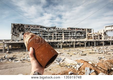 Unexploded 120 mm artillery shell in hand with destroyed Donetsk airport ruins on background poster