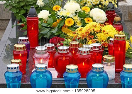 Flowers and votive candles which glows on the grave lantern