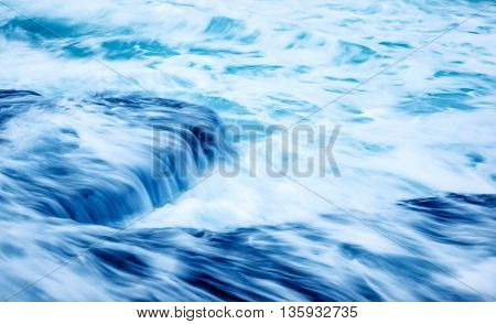 Slow motion waves background, beautiful stormy sea, streaming water on the rocks, abstract blue natural background