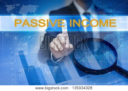 Businessman hand touching PASSIVE INCOME button on virtual screen