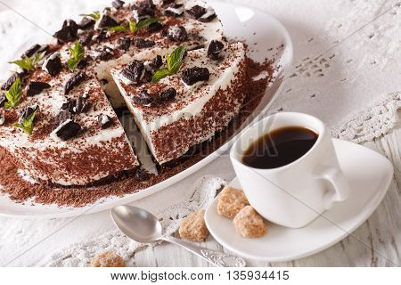 Cheese Cake With Pieces Of Chocolate Cookies And Coffee Close-up. Horizontal