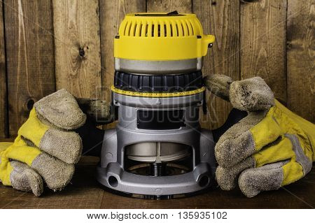 hand held electric fixed base router on wood background with leather work gloves