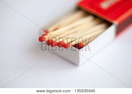 Wooden match in the box on the white