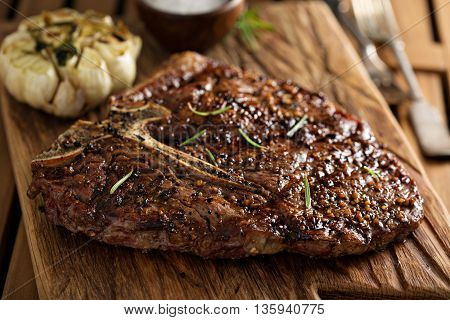 Tbone beef steak cooked on a grill with rosemary and garlic