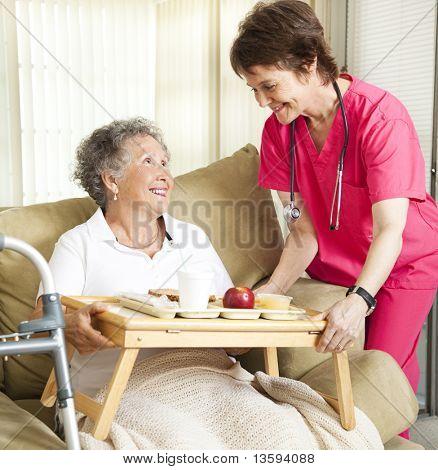 Ehemaliger senior Woman im Pflegeheim wird Mittagessen aus einer fürsorglichen Krankenschwester.