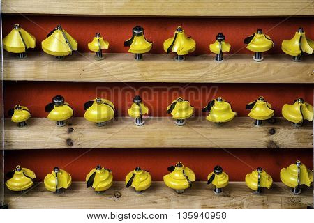 wooden cabinet displaying yellow metal router bits on red background