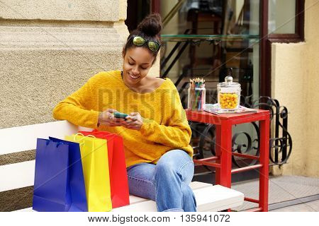 Female Shopper Outdoors On Bench Using Mobile Phone