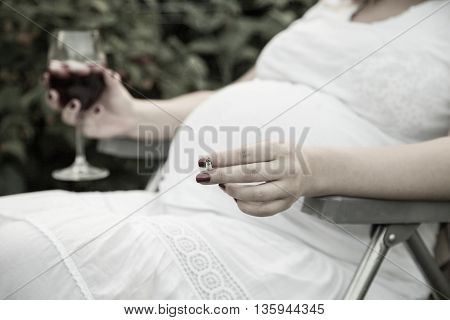 Young pregnant woman holding wine and cigarette