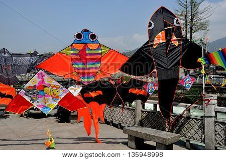 Dujiangyan China - April 8 2011: Colourful kites are displayed alongside the Min River quay