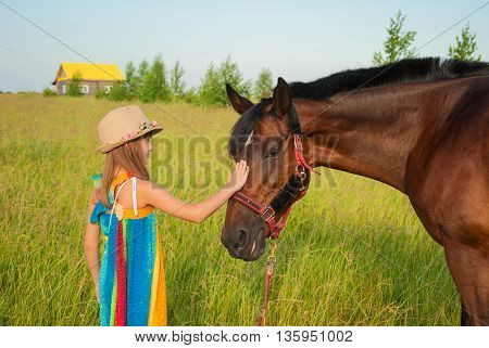 Little girl in a bright dress and hat gently stroking horse