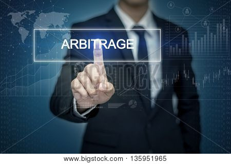 Businessman hand touching ARBITRAGE button on virtual screen
