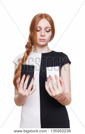 Young redhead woman choose between two cell phones. Girl looks at mobile, selecting color - black or white. Comparing smartphones in her hands. Female portrait isolated at white background