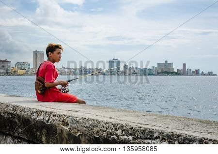 HAVANA - CUBA JUNE 20, 2016: Boy fishing from the seawall of the Malecon with the city skyline in the distance.