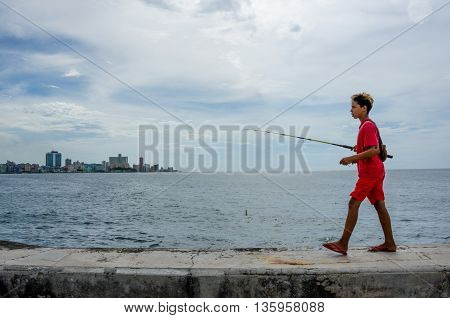 HAVANA - CUBA JUNE 20, 2016: Boy with a fishing rod walking along the seawall of the Malecon with the city skyline in the distance.