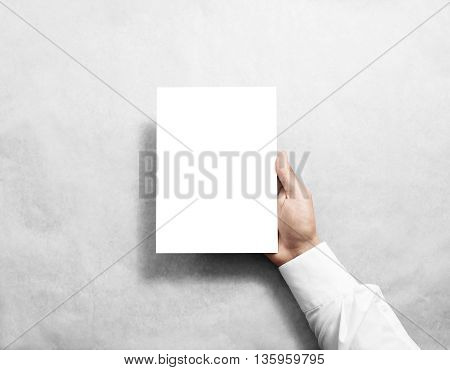 Hand holding blank white brochure booklet in the hand. Leaflet presentation. Pamphlet hold hand. Man show book offset paper. Sheet template. Booklet design. Paper sheet display read first person