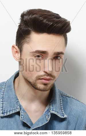 Portrait of young model man demonstrating his gorgeous and luxurious hair in studio. Handsome male in jeans shirt over shite background.