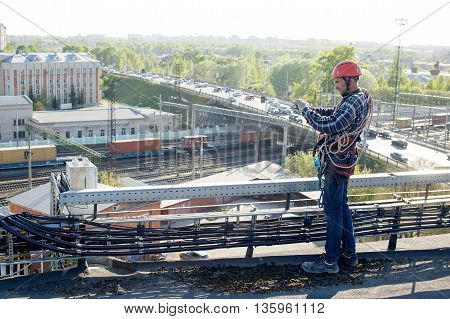 quality control. worker finished work and takes photos for the report. tower technician installed telecommunication equipment on the roof of the building