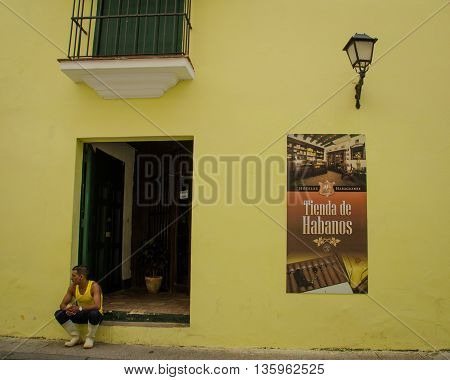 HAVANA - CUBA JUNE 19, 2016: A man sits on the stoop of his home which has been recently painted bright yellow. A poster selling cigars is posted on the wall.