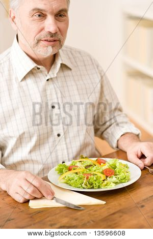 Senior mature man eat vegetable salad at wooden table poster