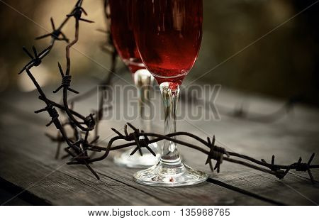 Glasses with alcoholic drink and a rusty barbed wire on a wooden table. Alcoholic dependence.