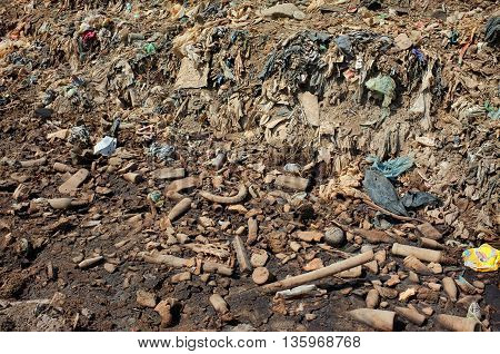 BALI INDONESIA - APRIL 30: Plastic household rubbish and poisonous industrial waste contaminates soil land and water at a polluted landfill site on April 30 2016 in Suwung Bali Indonesia.