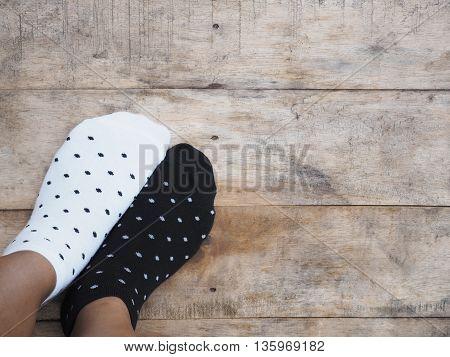 Selfie feet wearing black and white polka dot socks on wooden floor background