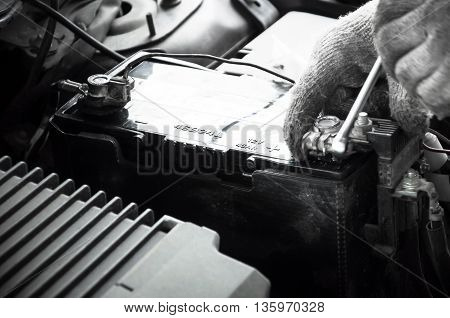 motion blur of Mechanic engineer fixing car battery in garage