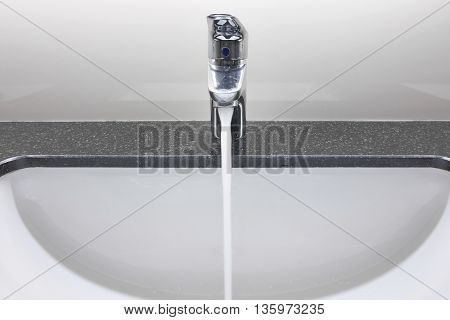 White Washbasin And Faucet On Granite Counter With Water Drop
