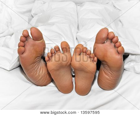 Mother And Child Feet Under The Sheets