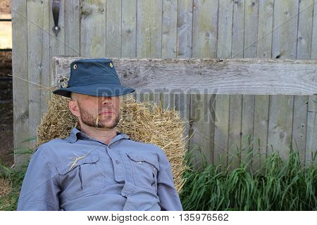 Farm hand resting on a bail of hay.