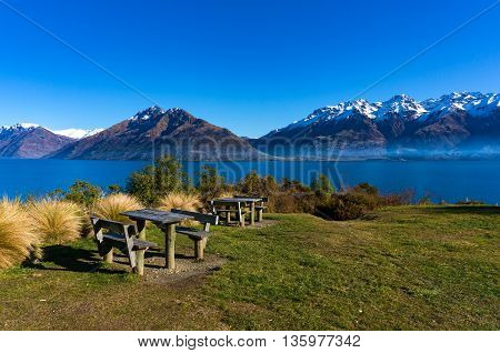 Outdoor rest area with winter mountain landscape on the background. Picnic tables on a hill with lake and mountain view. New Zealand