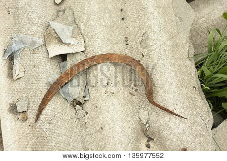 old rusted sickle on roofing slate close up