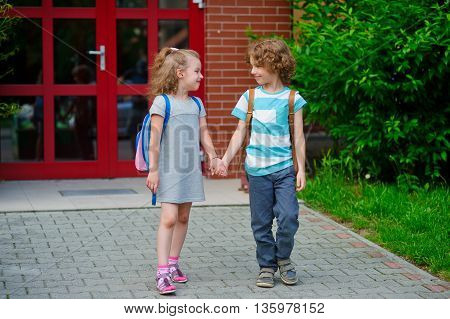 Two first graders on a schoolyard. The boy and the girl go having joined hands. Behind shoulders at school students satchels. Children look at each other and smile.