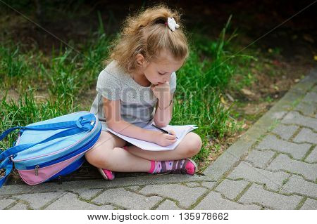 The little schoolgirl sits having crossed legs on a grass and something writes to a notebook. Girlie has a thoughtful look. Near the girl her satchel lies. Back to school.