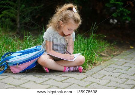 Schoolgirl of elementary school sits having crossed legs on a grass and something writes to a notebook. Girlie has a thoughtful look. Near the girl her satchel lies. Back to school.