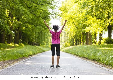 Beautiful mixed race African American young woman girl teenager fitness running jogging celebrating success on road lined with spring or summer green trees