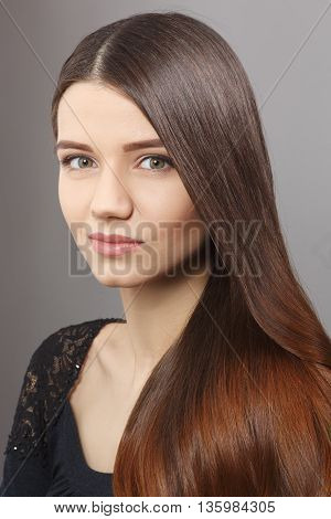 Portrait of young woman demonstrating her long brownhair in studio. Beautiful lady with modern hairstyle over grey background.
