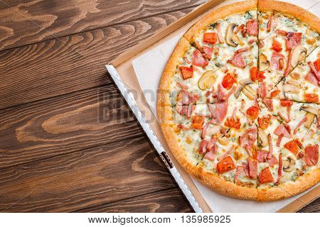 Delicious pizza with mushrooms and ham served on wooden table, top view