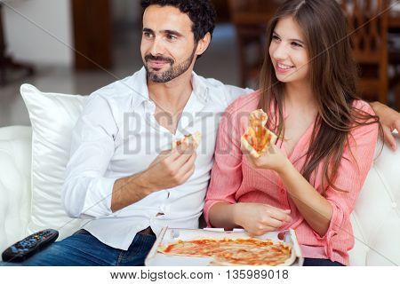 Happy couple watching tv while eating pizza