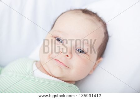Portrait of happy newborn baby in bed