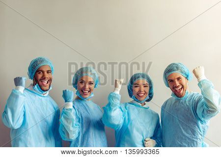 Surgeons of different nationalities and genders in medical wear are ready for the operation showing fists looking at camera and smiling