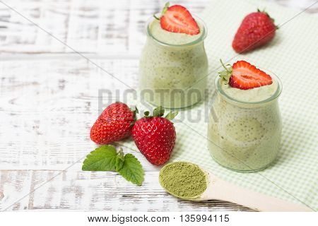 Matcha green tea chia seed pudding dessert with fresh mint and strawberry on a gray background. Healthy breakfast. Superfoods.