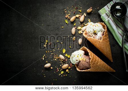 Ice cream with chocolate and pistachios on a dark slate background.