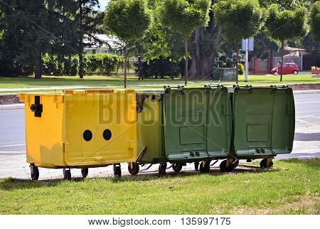 One yellow and two green dumpsters on the street